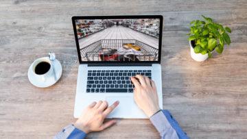Mani di un uomo che digitano su un laptop con l'immagine di un carrello della spesa